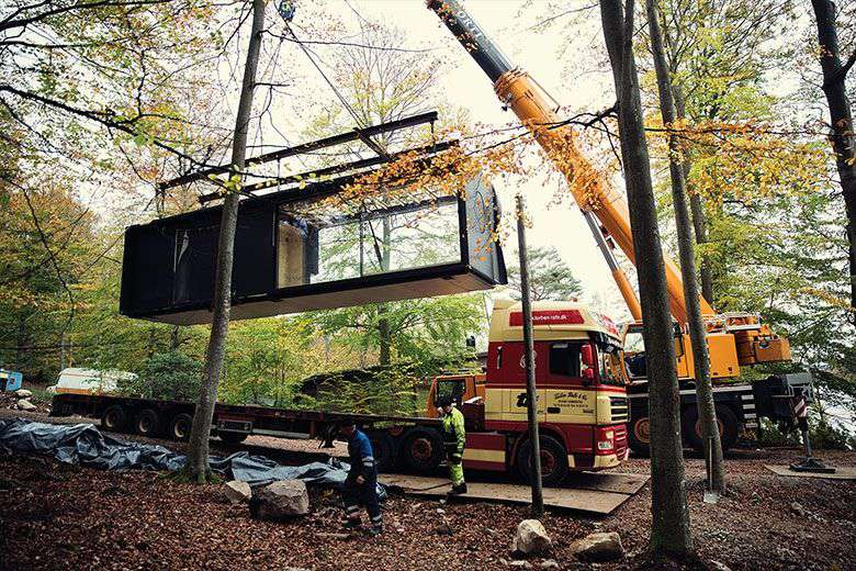Truck and crane lifiting VIPP unit for installation among trees