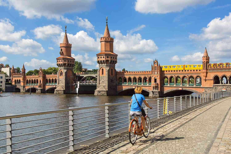 A biker rides past a body of water in Berlin