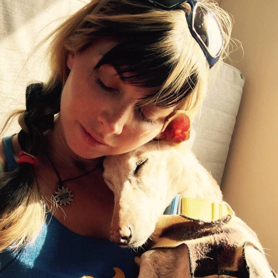 A dog cuddles up to Tina Solera