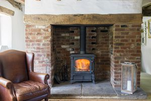 A wood stove in a brick fireplace, with a leather chair nearby