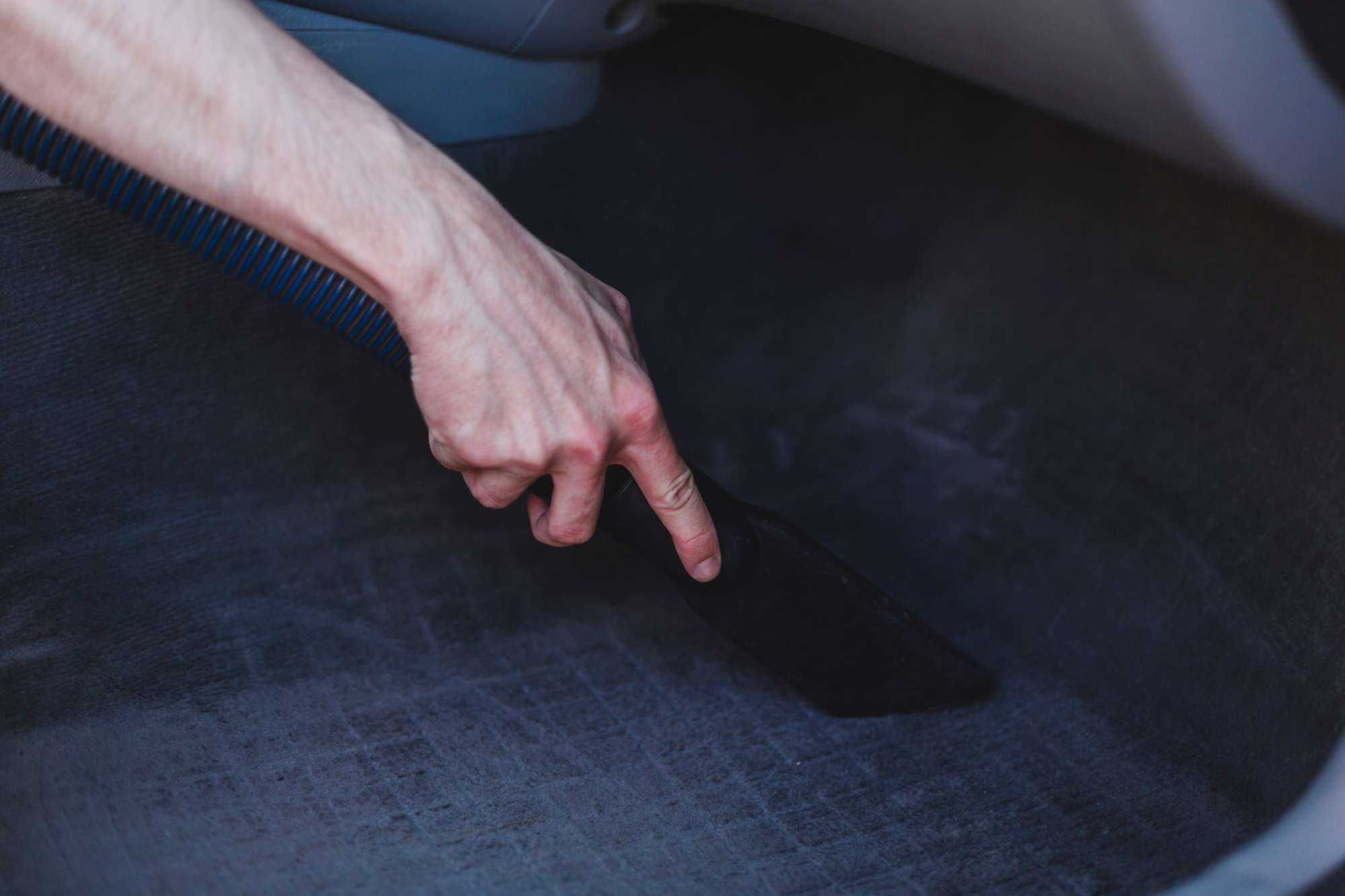 man cleans carpets in car