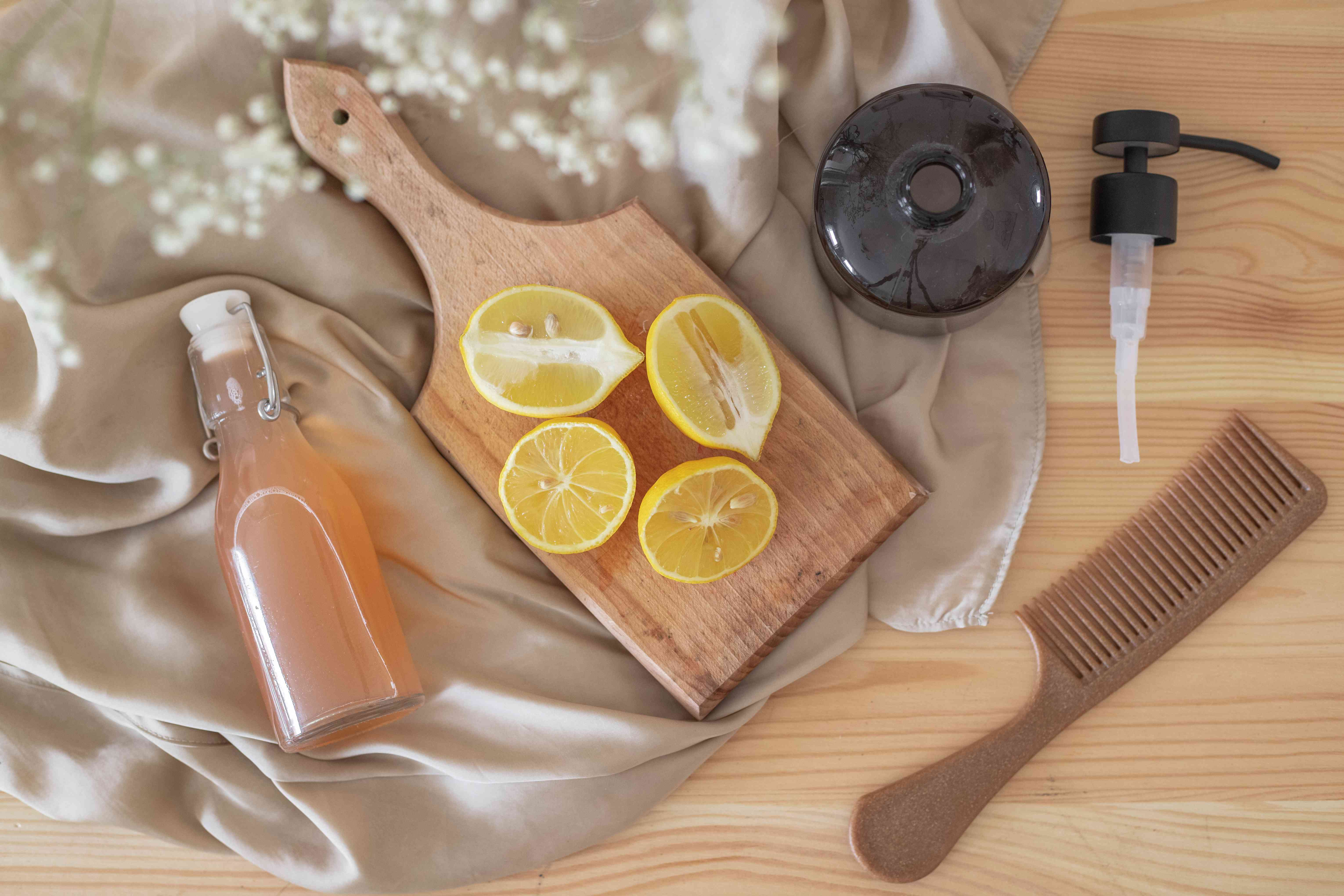 flat lay of apple cider vinegar in glass bottle with cut lemon slices on wooden cutting board