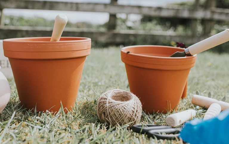 Two fresh, new, clean terracotta pots in a garden, in front of a fence. A plant, string, and various other gardening equipment in the foreground.