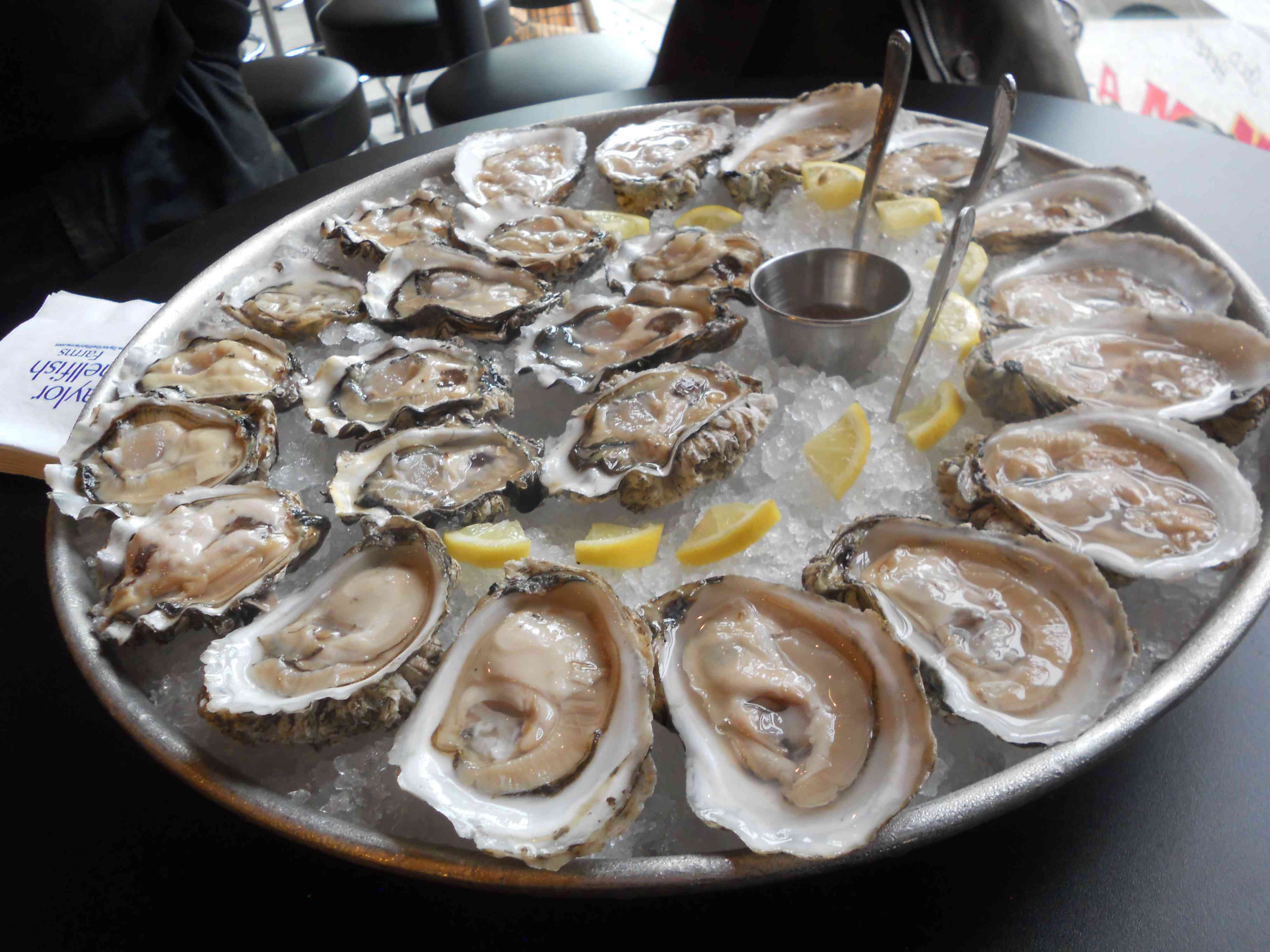 A plate of iced oysters with lemons and knives