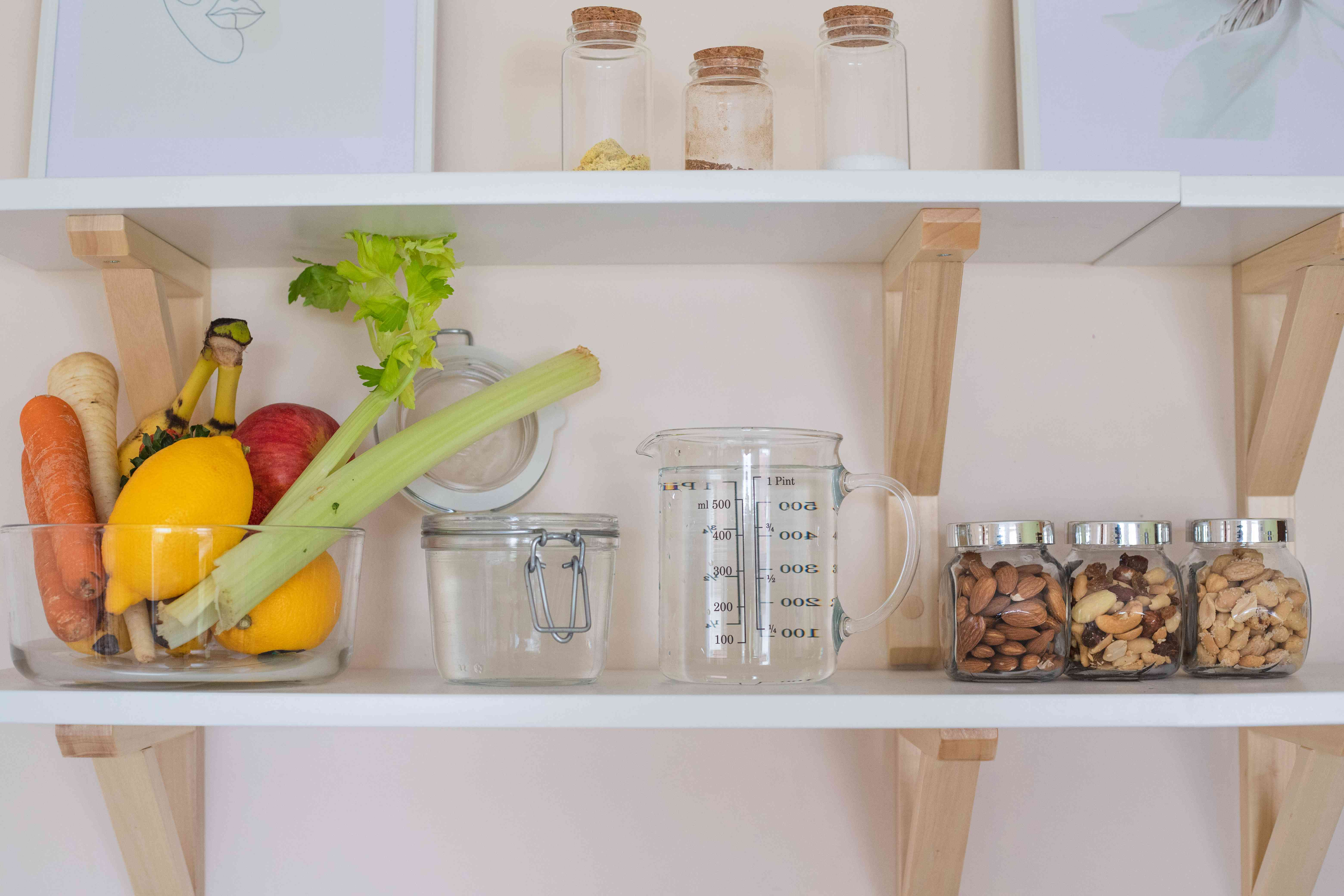 kitchen display open shelves with healthy vegetables, nuts, and glass jars