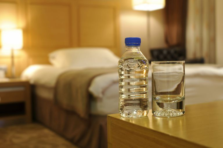 A water bottle and glass set on a table in a hotel suite.