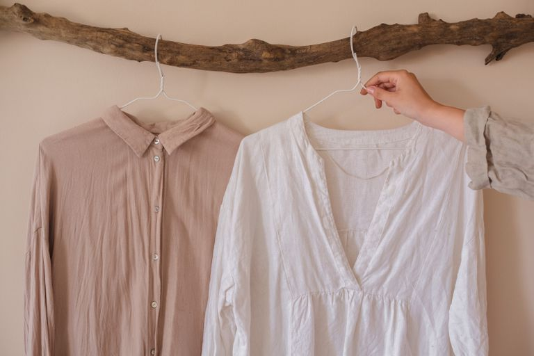 side by side linen and cotton shirts hang from upcycled piece of driftwood