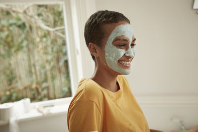A young black woman with a green facial mask.