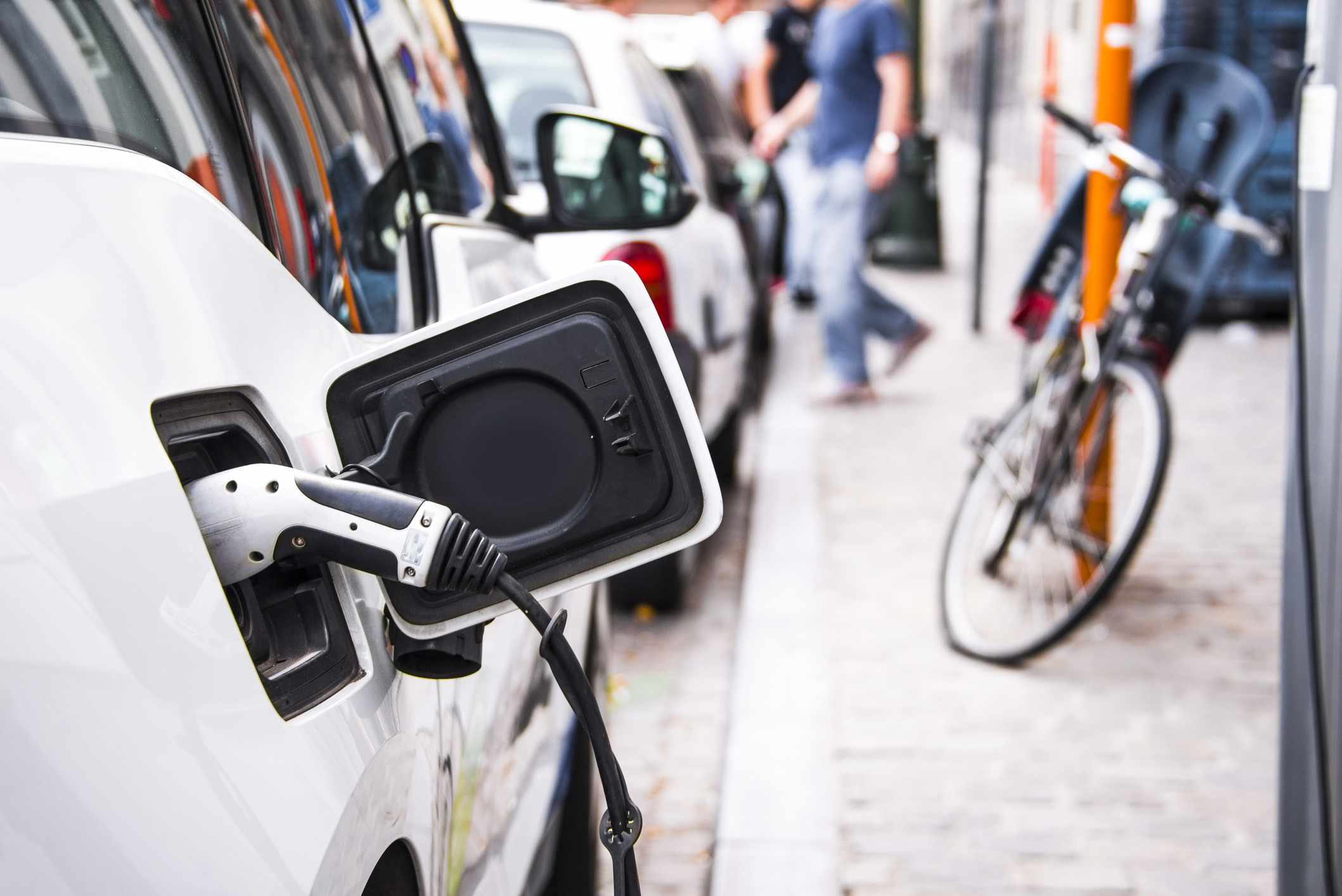 Electric vehicle plugged in on sidewalk