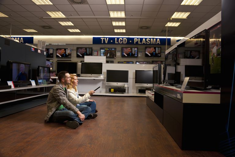 Couple sitting on the floor looking at TVs in a store