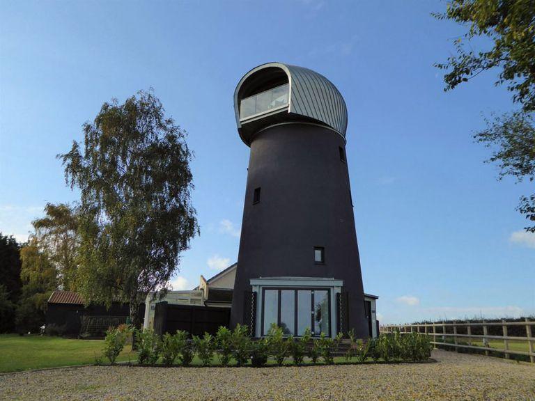 Molino de viento abandonado convertido en una casa de huéspedes única con módulo de visualización revestido de metal