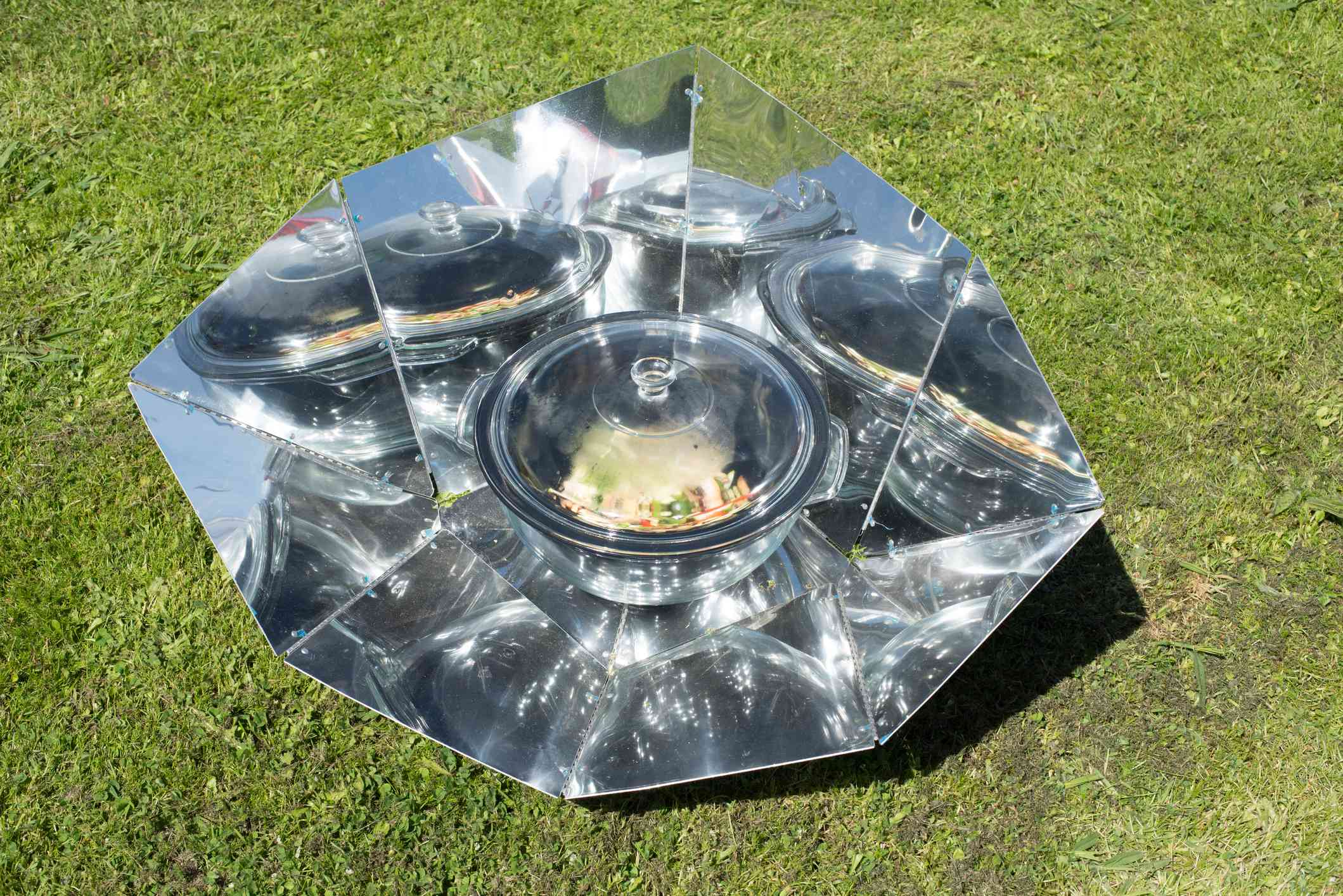 Cooking in a solar oven on the grass.