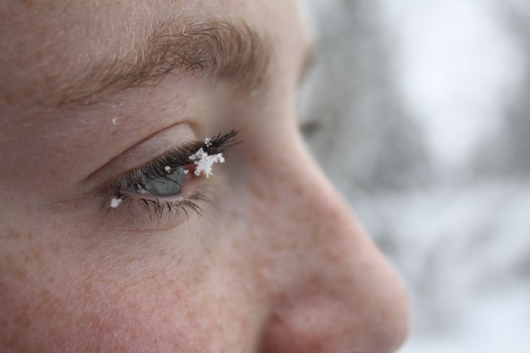 A woman with freckled skin has snow on her eyelash in the winter.
