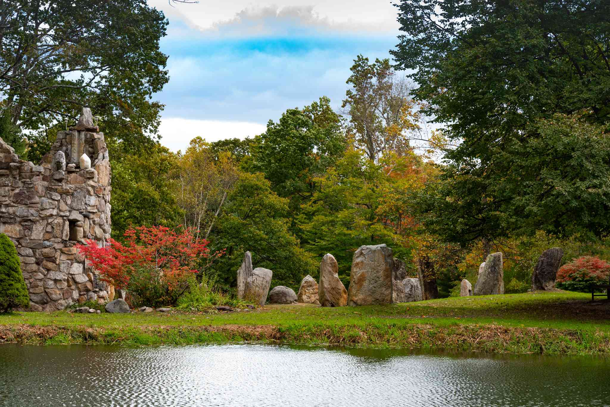 A stone bell tower and circle of stone structures with a pond in the foreground