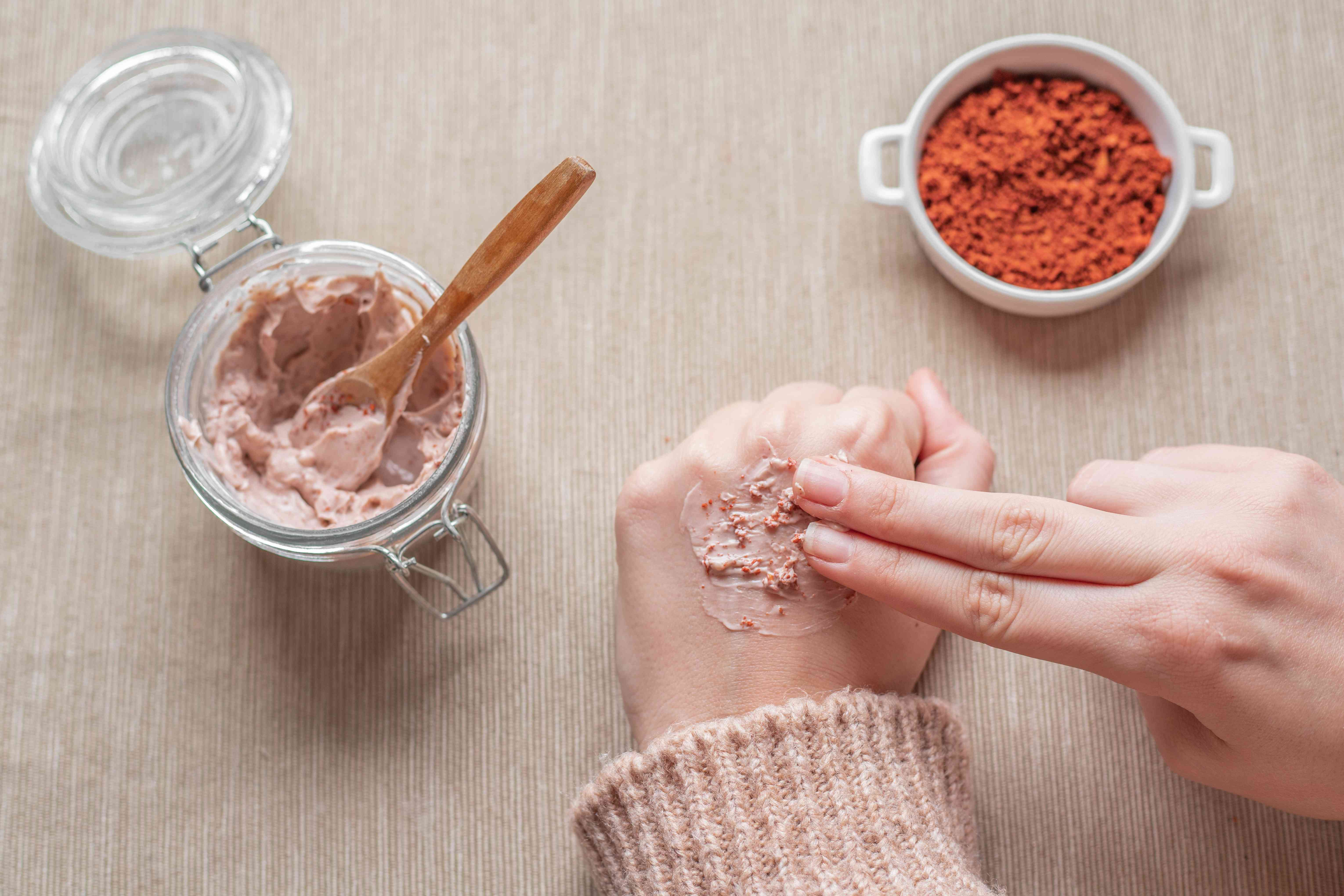 hands rub a pink avocado pit face mask on hands