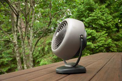 retro-looking gray fan outside on wooden deck in woodsy backyard