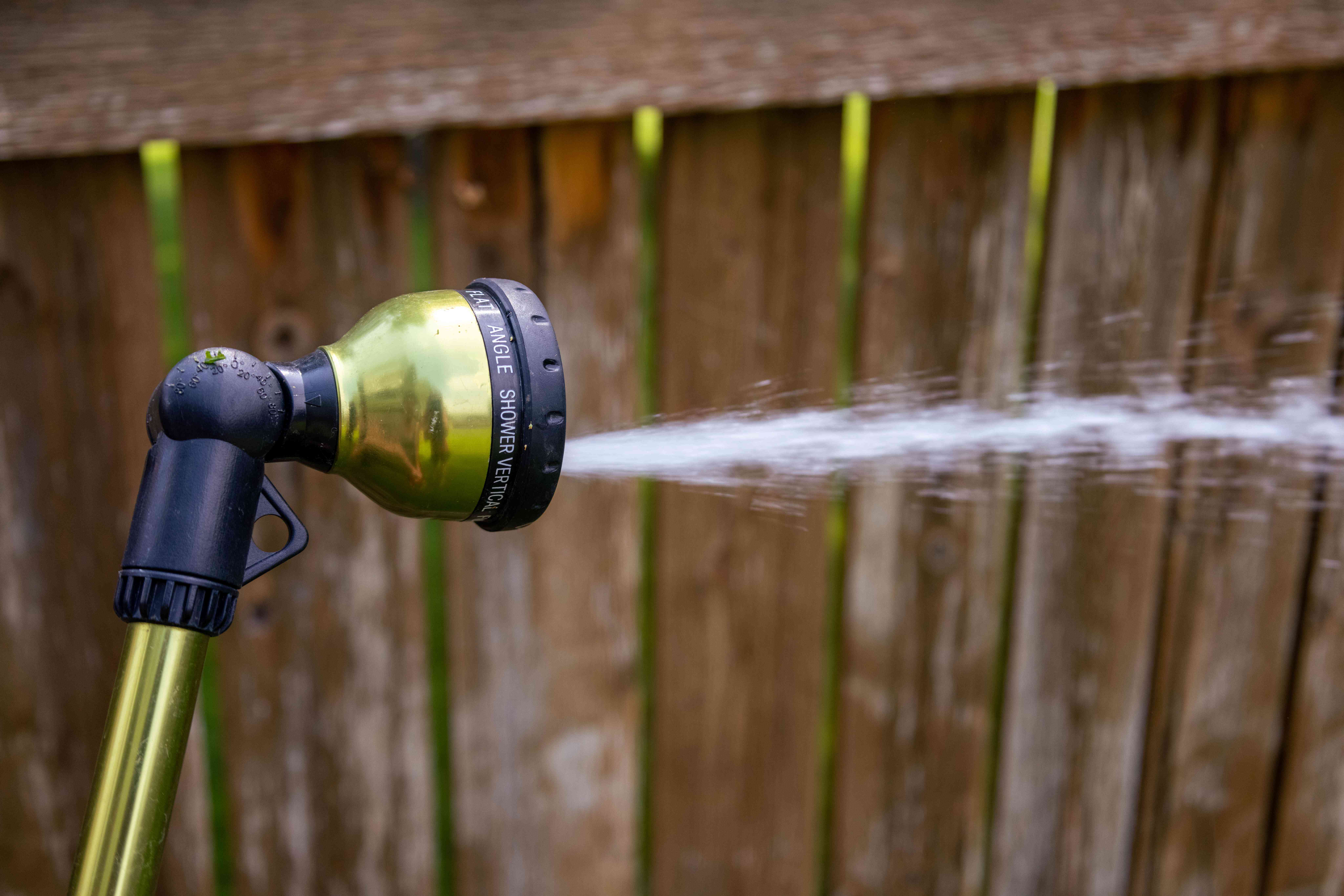 hose with nozzle attachment is sprayed outside in yard next to wooden fence