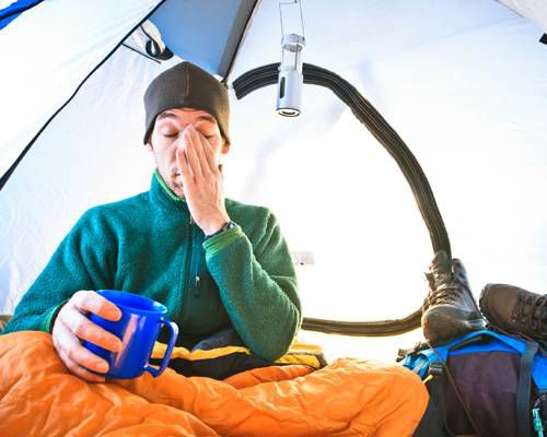 Person in a tent holding a coffee cup and rubbing face with left hand