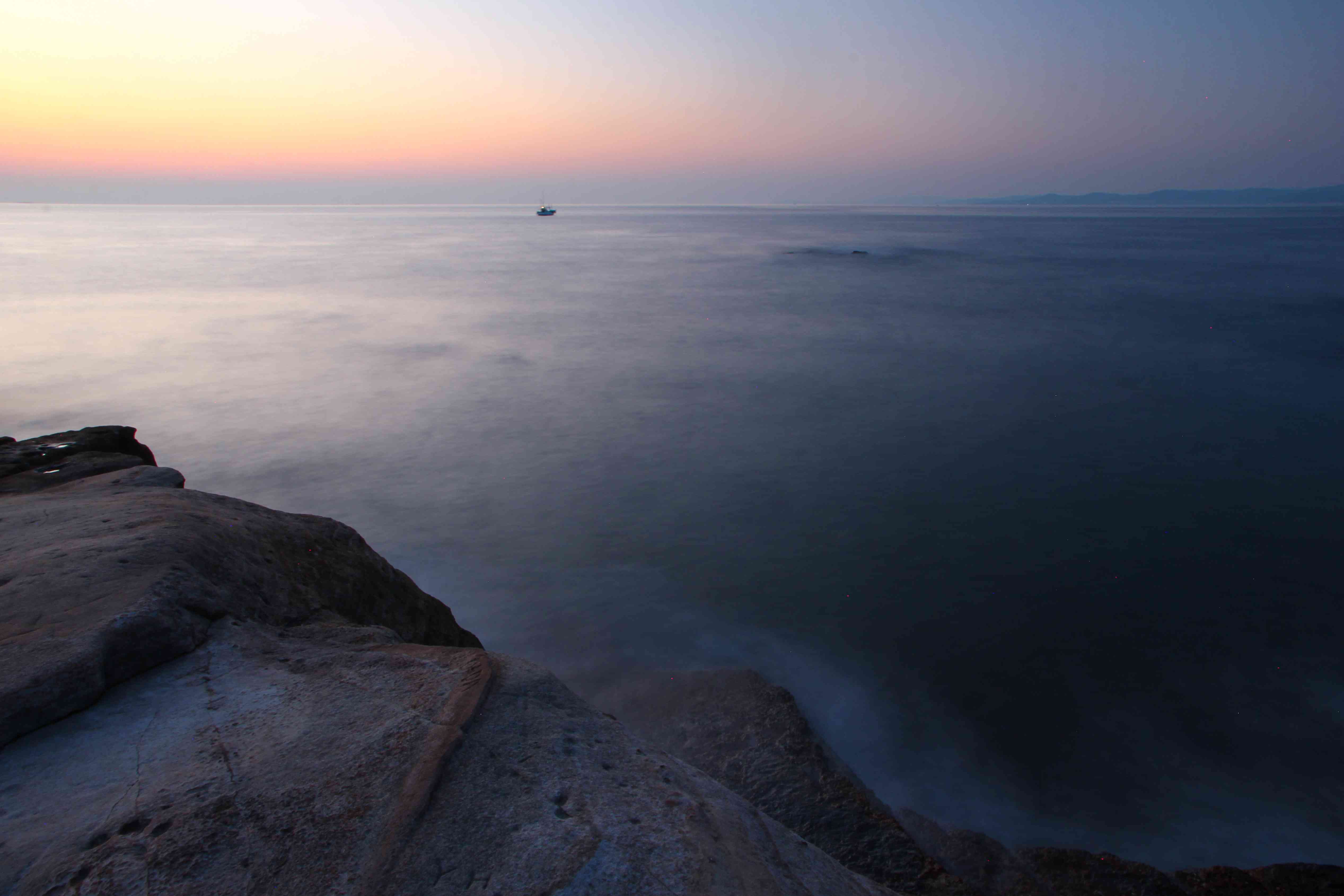 spooky shot of ocean at sunrise along coast with fog and small ship on horizon