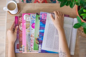 overhead view of hand on multiple magazines spread on a table with coffee cup
