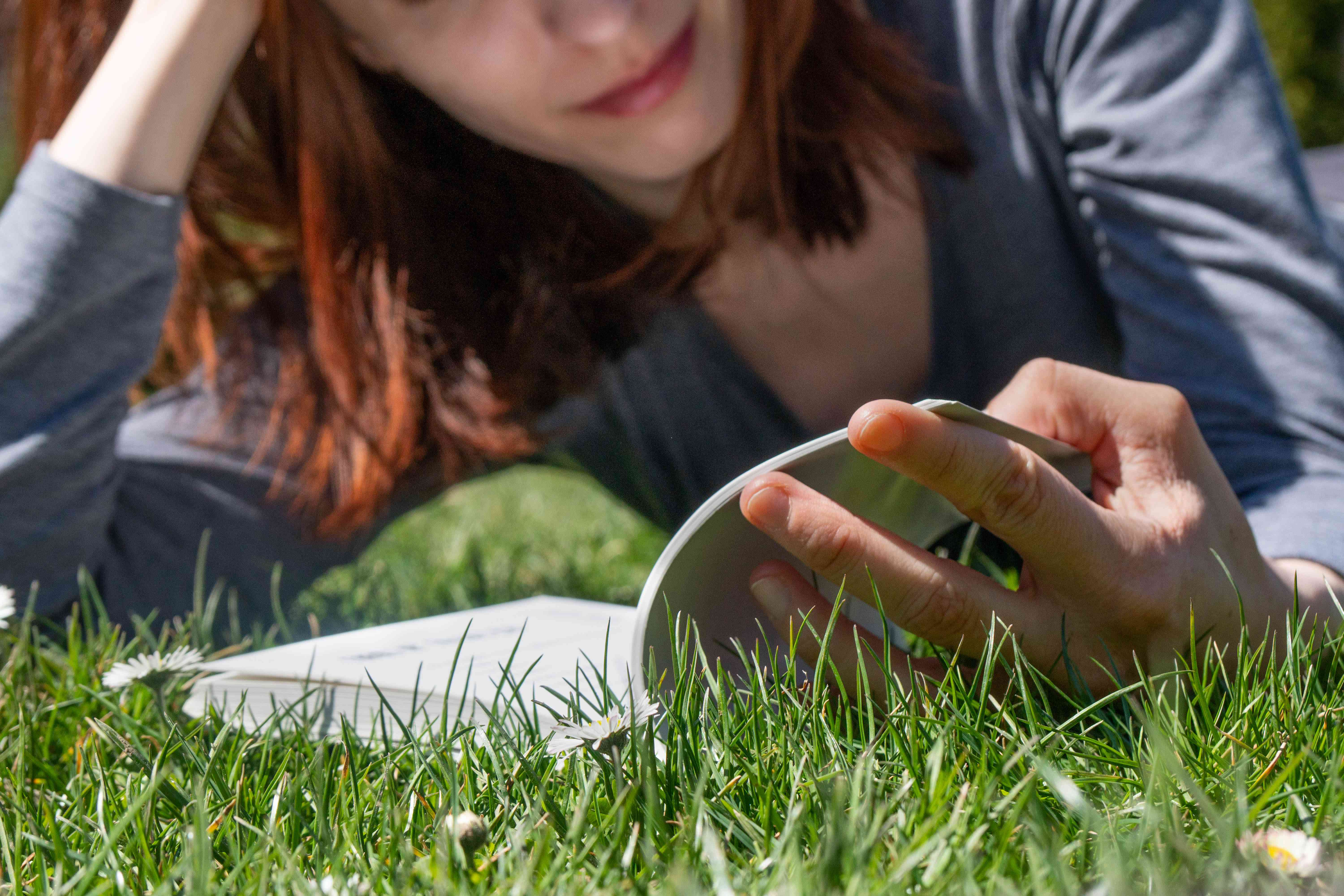ground shot of woman laying in green grass while reading book on a sunny day