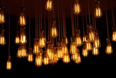 Several yellow-hued lightbulbs hanging from the ceiling