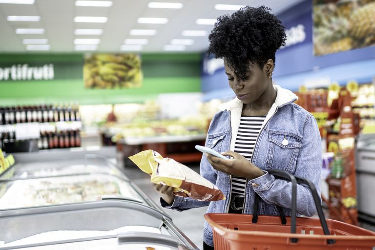 A Black woman looks at chip ingredients on her phone at grocery store.