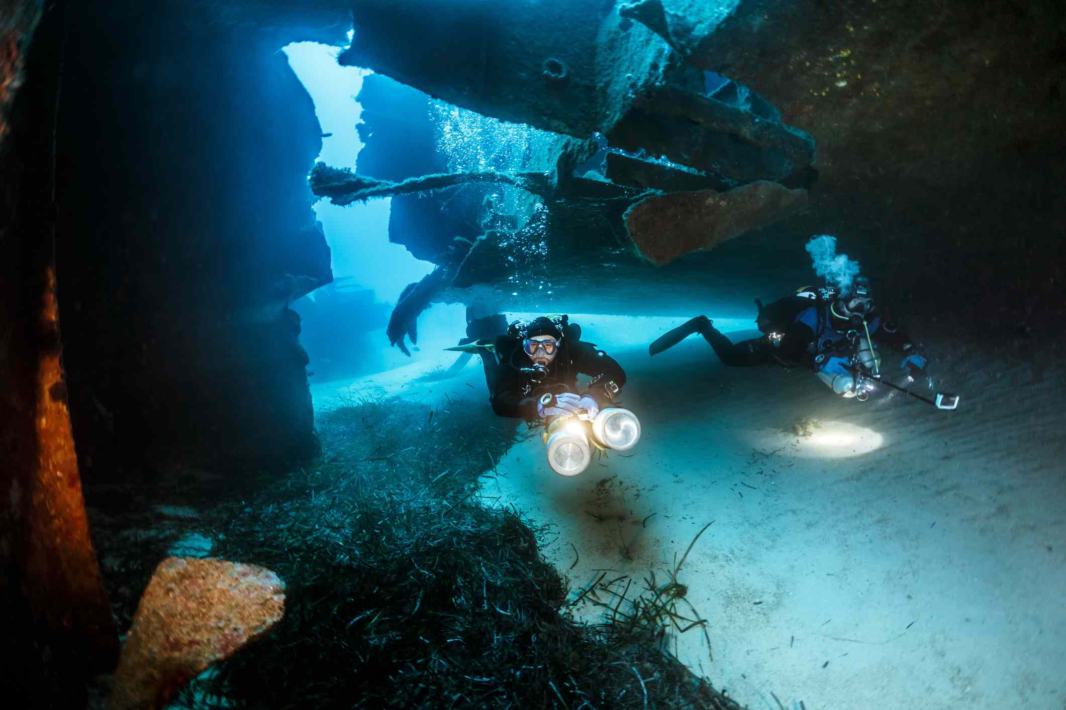 Two scuba divers with bright lights swimming through the wreck Um El Faroud in Malta