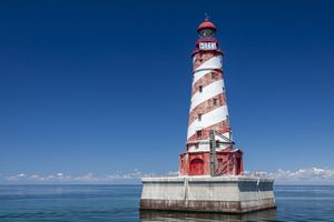 Red and white striped lighthouse surrounded by water