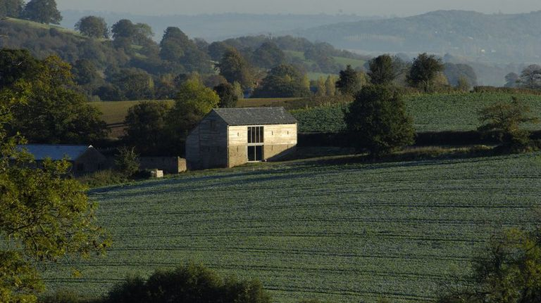 Cottage against a sweeping countryside of rolling hills and fields