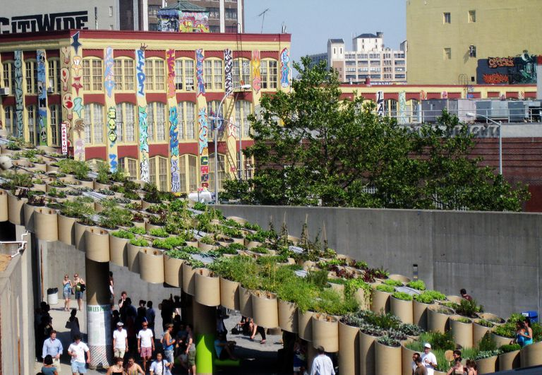 An urban farm with cylinders growing food outside of an art gallery.