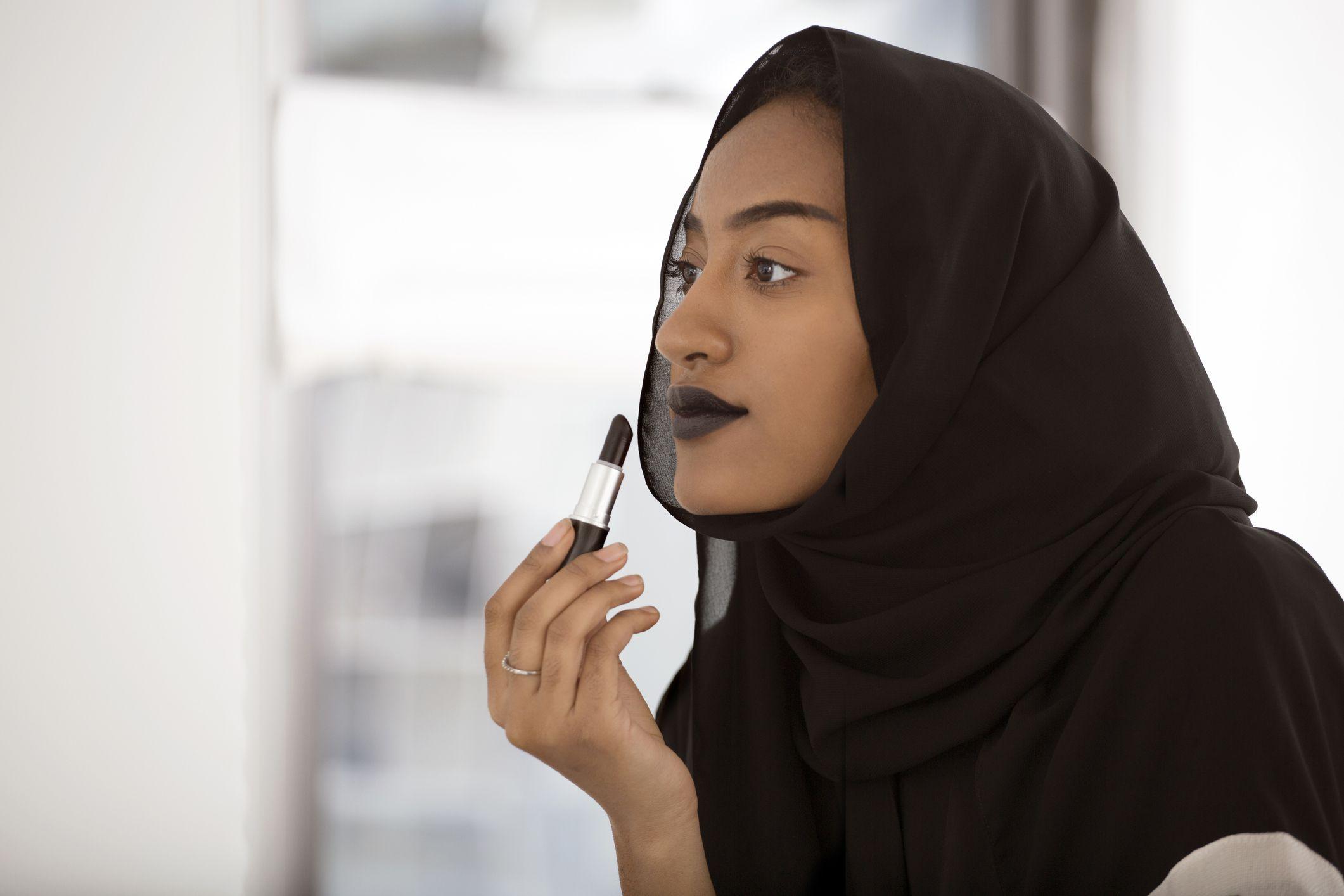 A muslim woman applies dark lipstick in the mirror.