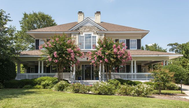 Crepe myrtles bloom in front of a house