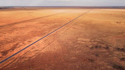 A desert outback area in Australia with a road running through it.