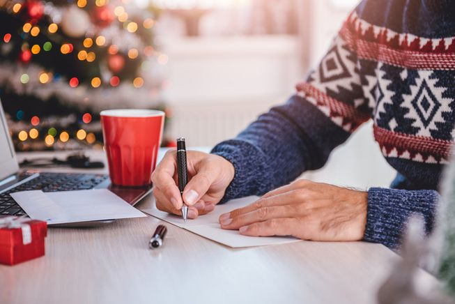 A person in a sweater writes in a Christmas card at a desk near a Christmas tree