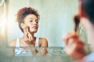 Woman using a makeup brush in the mirror