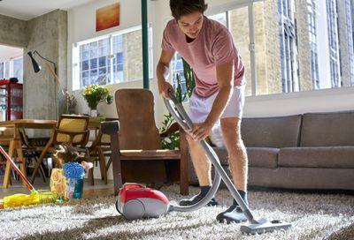 man vacuuming a rug