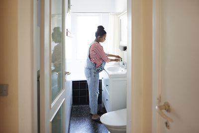 open door shows pregnant woman in overalls washes hands in bathroom sink