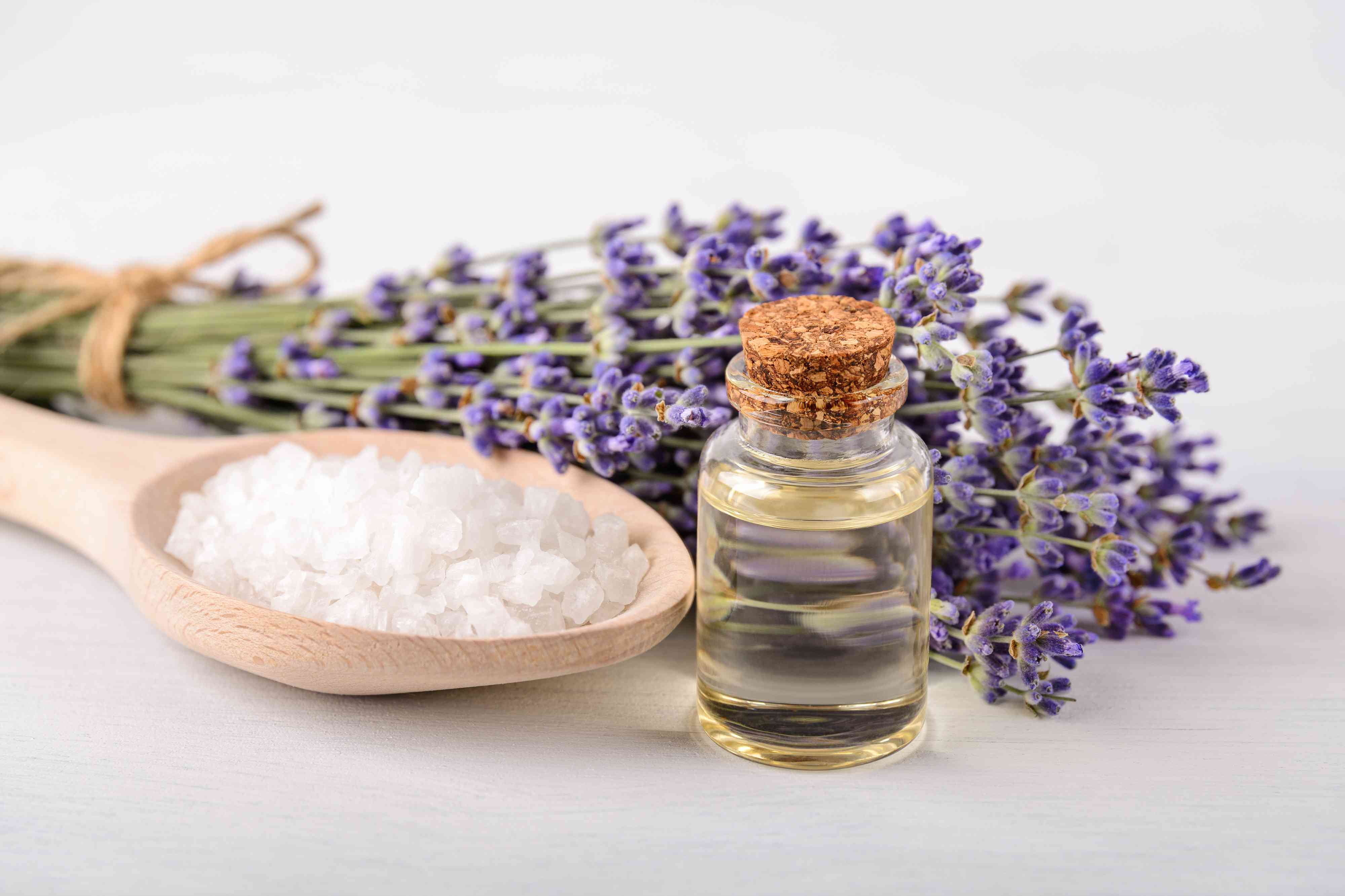 Lavender essential oil, cosmetic bath salt in a wood spoon and fresh fragrant lavender on a white wood surface. Home made spa, skincare and cosmetology concept.