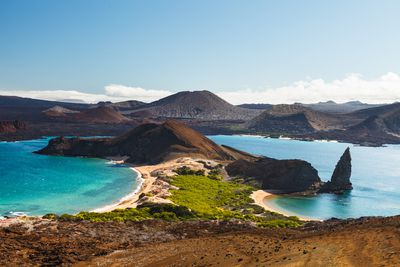 View on the volcanic landscape of Bartolome Island with famous Pinnacle Rock and Golden Beach, Galapagos Islands, Ecuador