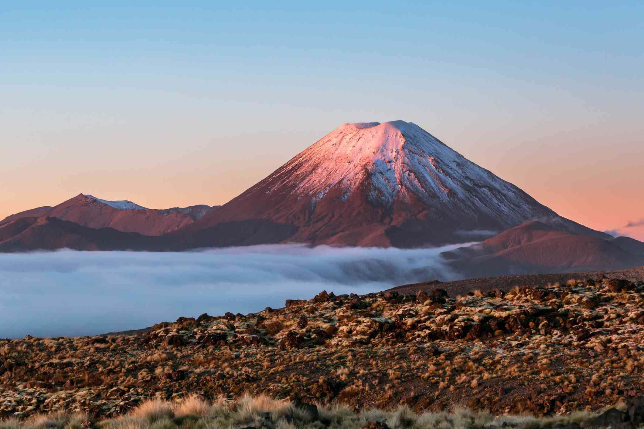 View of snowcapped Mt. Ngauruhoe volcano under a blue and orange sky at sunset in Tongariro National Park, North Island, New Zealand