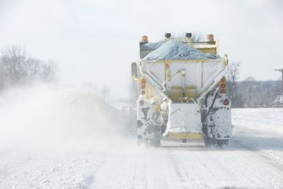 Snow plow applying road salt