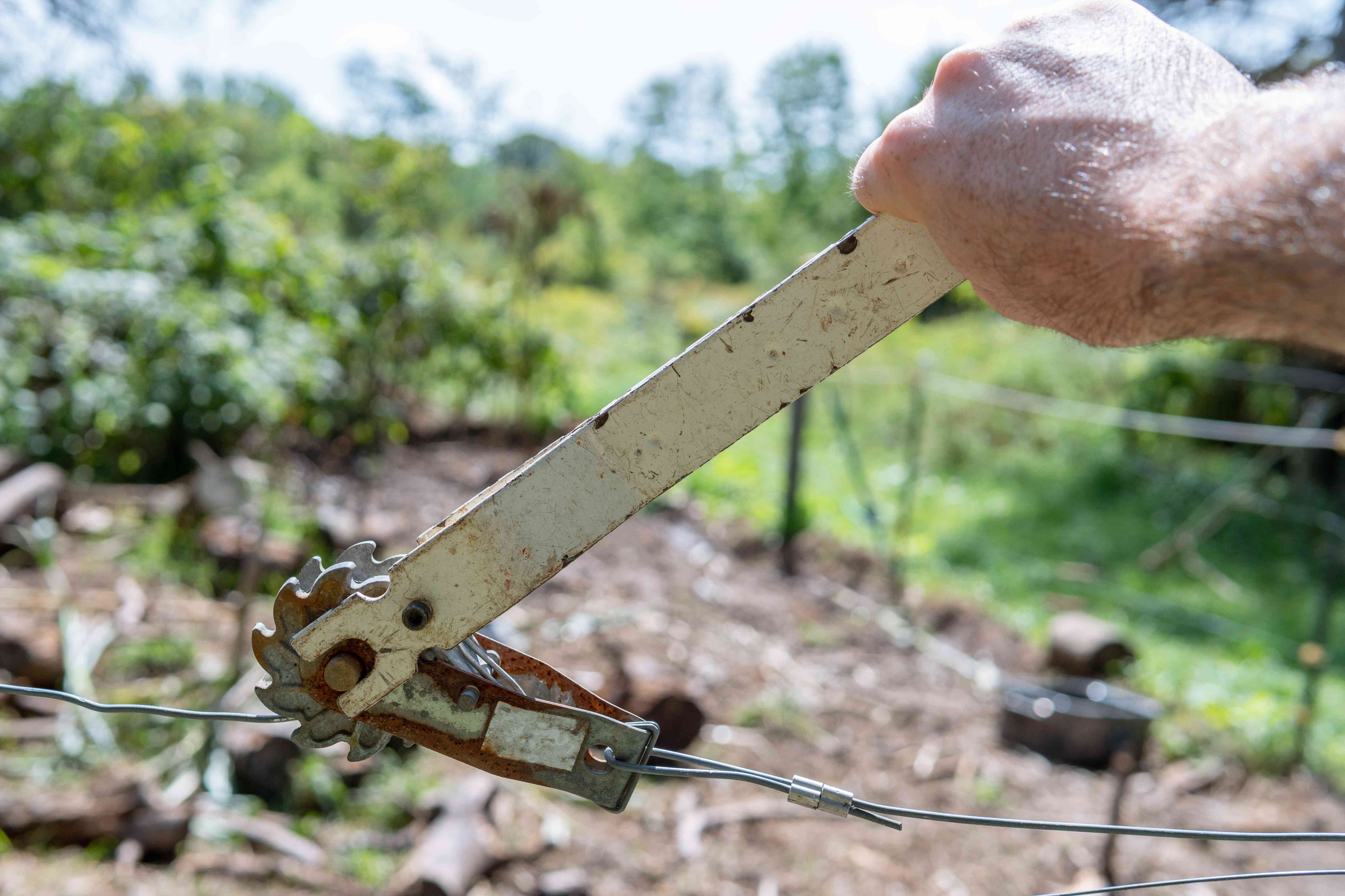 hand uses fence tensioner on fence outside
