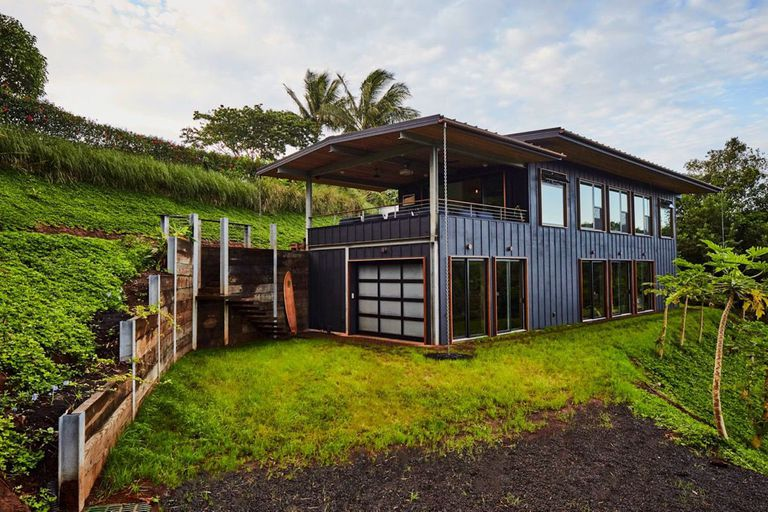 Two-story rectangular house with an upper deck on a tropical green hillside