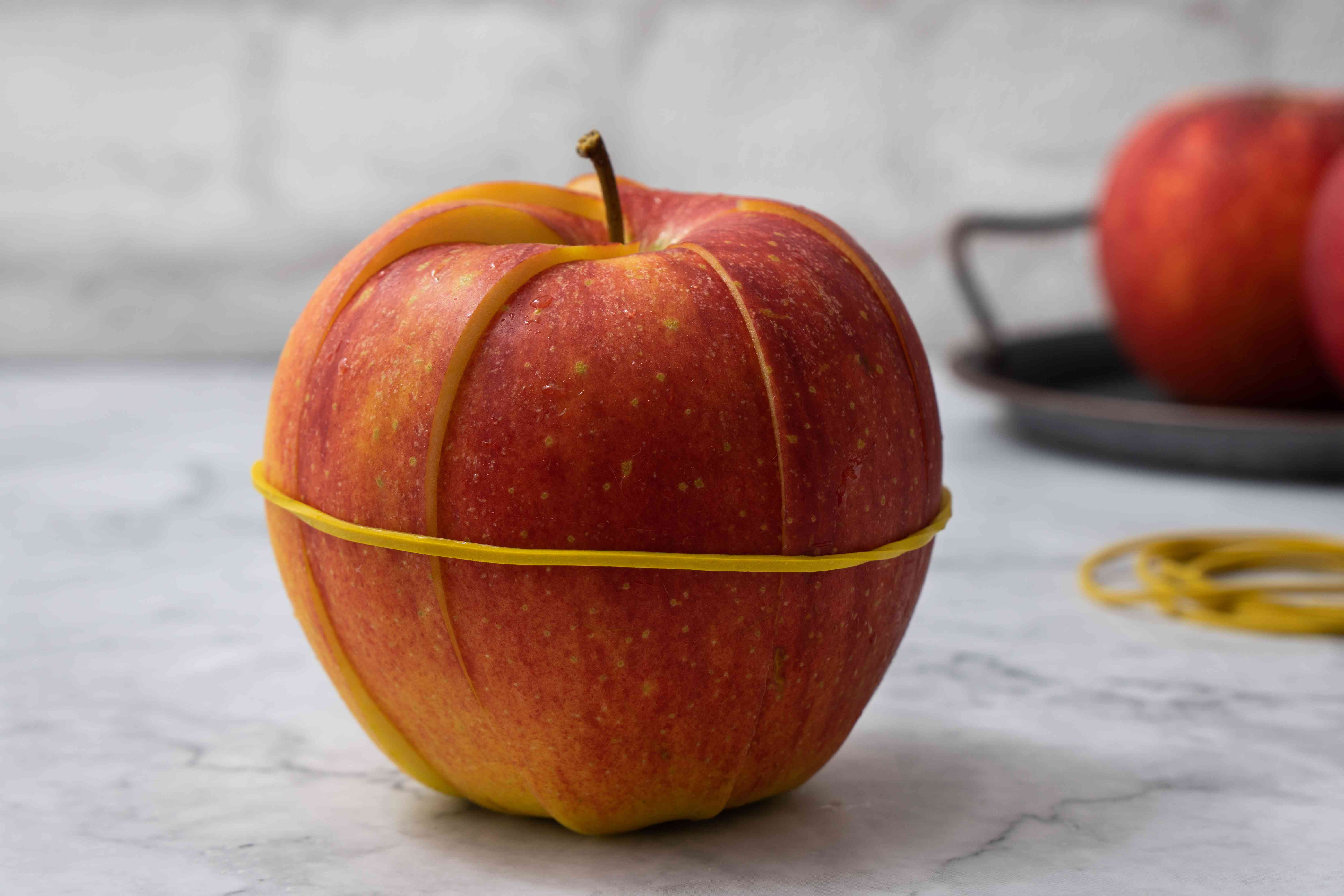 sliced apple held with yellow rubber band
