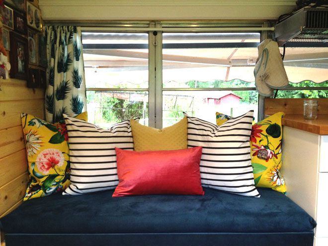 A blue bench seat against a window, with multicolored pillows