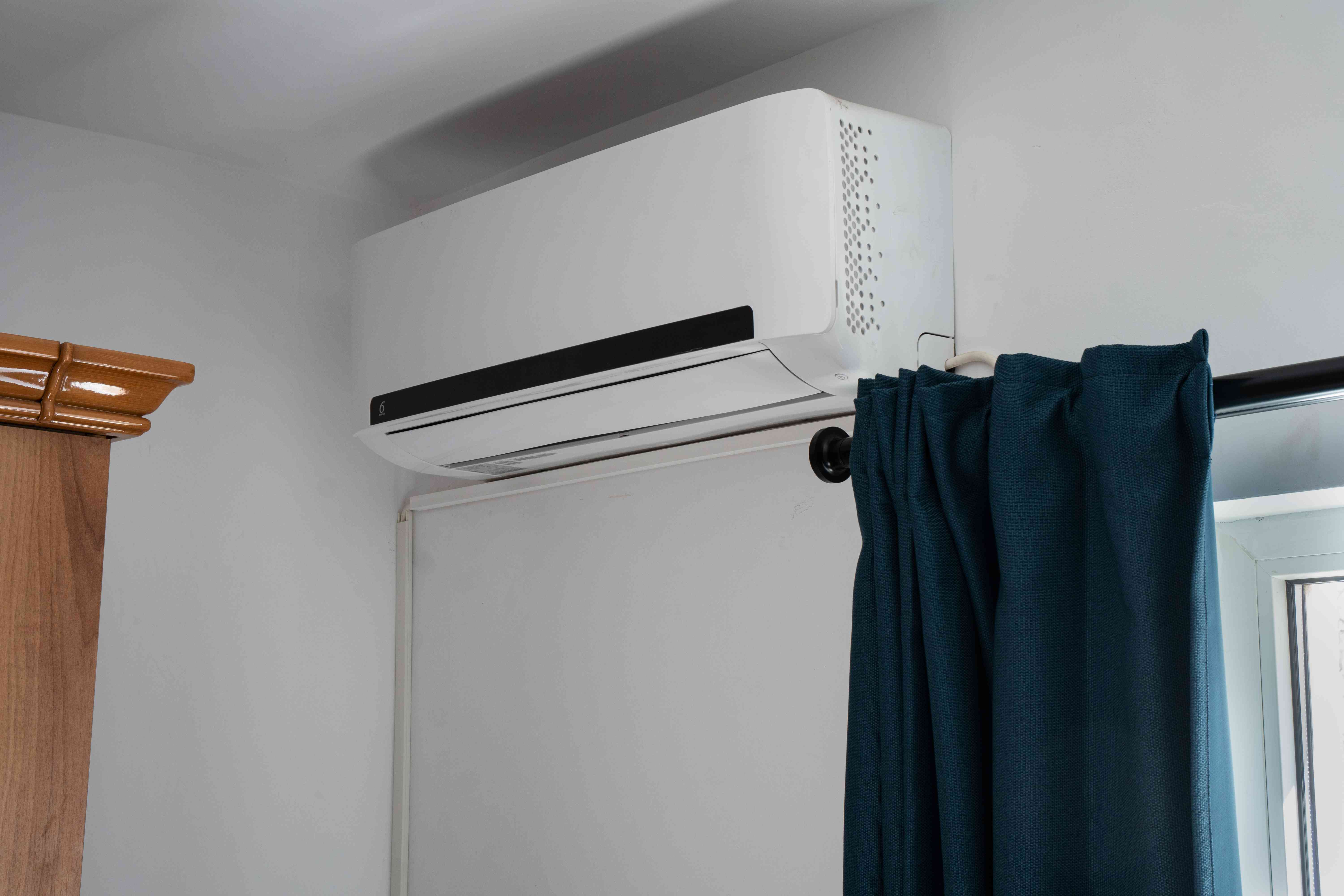 Shot of split air conditioning home unit on white wall near window with hanging curtain