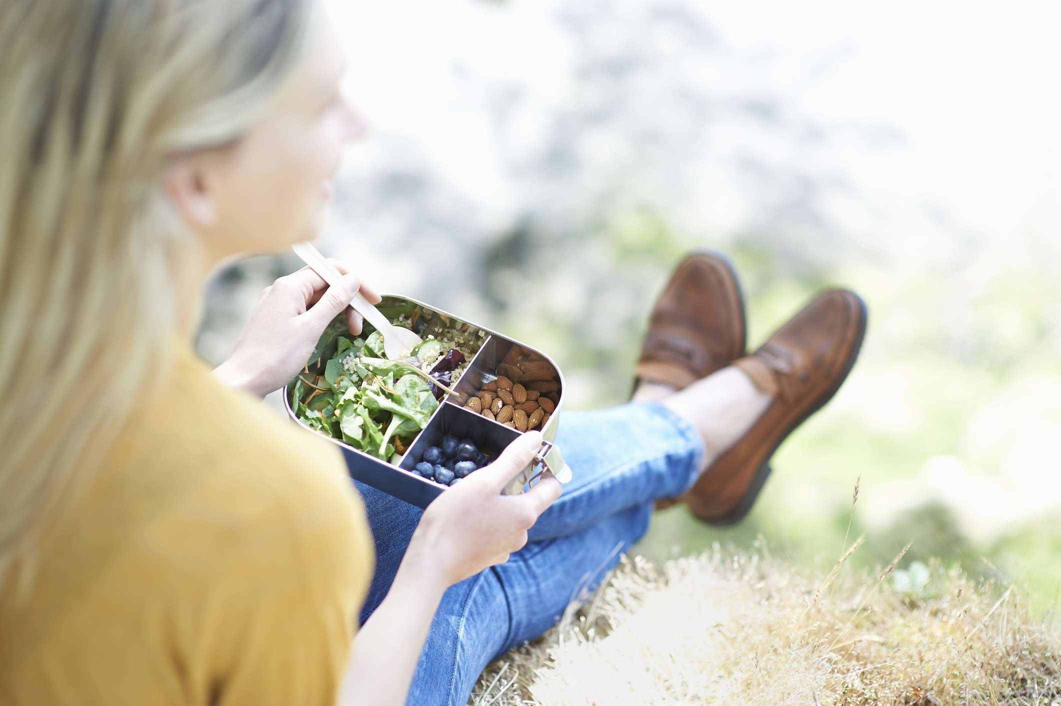 A white woman eats a vegan lunch from a metal container.