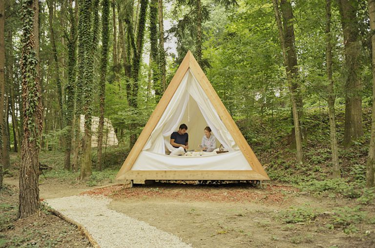 People in an a-frame cabin surrounded by trees