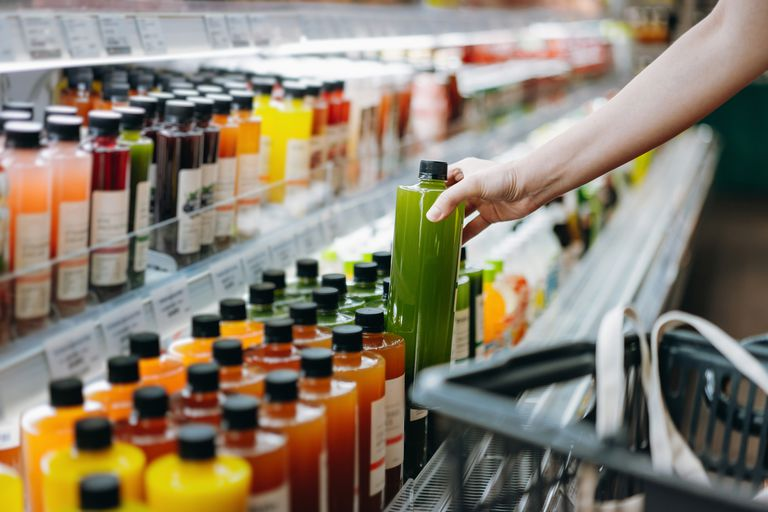 Shopper reaching for a green drink in the juice aisle